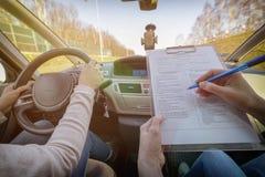 Prüfer, der Fahrer ` s Lizenzstraßenversuchform ausfüllt Stockfotos