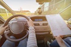 Prüfer, der Fahrer ` s Lizenzstraßenversuchform ausfüllt Lizenzfreie Stockfotos