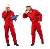 Prüfer in der roten Uniform und im weißen Hardhat bei der Arbeit stockfoto