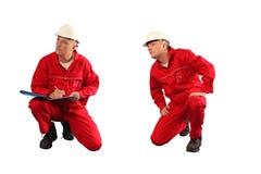 Prüfer in der roten Uniform und im weißen Hardhat bei der Arbeit Lizenzfreie Stockfotos