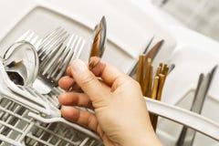 Prüfung auf Sauberkeit des Tafelsilbers von der Spülmaschine Lizenzfreie Stockfotos