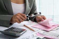 Prüfung der Rechnungen mit Vergrößerungsglas Stockfotografie