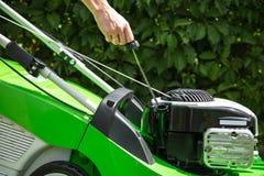 Prüfung des Öls in einem Rasenmäher. Lizenzfreie Stockbilder