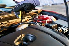 Prüfung des Maschinenölstandes im modernen Auto Winterservice für das sichere Fahren lizenzfreie stockbilder
