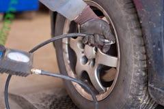 Prüfung des Reifendrucks an der AutomobilReparaturwerkstatt stockbild