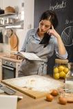 Prüfung des Rezepts im Kochbuch Frau, die amerikanische Torte zubereitet Stockbilder
