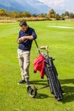 Prüfung von Mitteilungen auf dem Golfplatz lizenzfreies stockfoto