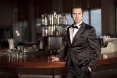prętowy przystojny mienia mężczyzna smokingu whisky Fotografia Stock