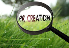 Pr creation. Magnifying glass with the word pr creation on grass background. Selective focus Stock Image