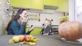 Pr?paration de Halloween La maman fait le maquillage à sa petite fille Se reposer dans la cuisine banque de vidéos