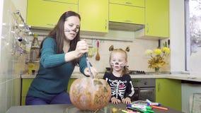 Pr?parations de Halloween La maman et la fille jouent dans le maquillage Coupez le potiron banque de vidéos