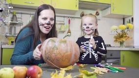 Pr?parations de Halloween La maman et la fille jouent dans le maquillage Potiron d'exposition banque de vidéos