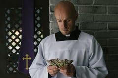 Pr?tre catholique comptant l'argent dans sa main images stock