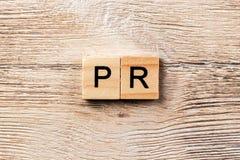 PR-woord op houtsnede wordt geschreven die public relationstekst op lijst, concept royalty-vrije stock afbeelding