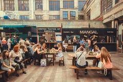 Praça da alimentação com a multidão de povos de relaxamento em torno das tabelas durante o festival exterior do alimento da rua Foto de Stock