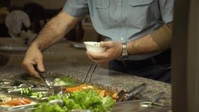 A praça da alimentação, um homem põe uma salada vegetal em um copo filme