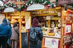 Praag, 15 December, 2016: De toerist bekijkt de goederen in de traditionele Kerstmismarkt Het vieren Kerstmis binnen Stock Foto