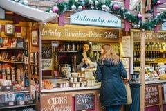 Praag, 15 December, 2016: De verkoper biedt de koper een brede selectie van honing en diverse wijnen aan Kerstmismarkt Royalty-vrije Stock Afbeeldingen