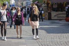 Praag, Tsjechische Republiek - 20 April, 2011: Drie jonge modieuze vrouwen glimlachen en lopen onderaan de straat royalty-vrije stock afbeelding