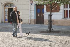 Praag, Tsjechische Republiek - 19 April, 2011: Een paar loopt in het vierkant met haar weinig hond Zij stellen voor een foto stock fotografie