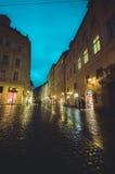 Praag, Tsjechische Republiek - 13 Augustus, 2015: Mooie gele voorgevels met de weg die van Bridgestone door op aardige regenachti Royalty-vrije Stock Foto's