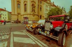 Praag, Tsjechische Republiek - 13 Augustus, 2015: Twee klassieke mooie die auto's op straat overdwars van beroemde Kerk worden ge Stock Foto's