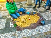 Praag, Tsjechische Republiek - 30 December, 2017: Een straatkunstenaar die een zandbeeldhouwwerk van hond maken stock fotografie