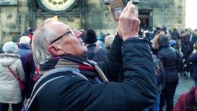 PRAAG, TSJECHISCHE REPUBLIEK - 3 DECEMBER, 2016 Hogere mens die in glazen foto's van oriëntatiepunten met zijn mobiele telefoon m Stock Afbeelding