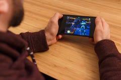 PRAAG, TSJECHISCHE REPUBLIEK - 16 MAART, 2019: Mens die een smartphone en playng de WONDERwedstrijd van Kampioenen mobiel spel ho royalty-vrije stock foto's