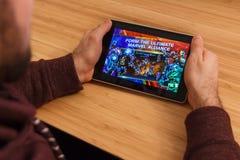 PRAAG, TSJECHISCHE REPUBLIEK - 16 MAART, 2019: Mens die een smartphone en playng de WONDERwedstrijd van Kampioenen mobiel spel ho royalty-vrije stock foto