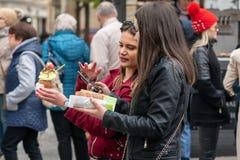 PRAAG, TSJECHISCHE REPUBLIEK - 12TH APRIL 2019: De vrouwelijke toeristen eten marktvoedsel tijdens de Pasen-festiviteiten in Praa stock foto's