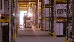 Prac forklifts w magazynie Forklift z pude?kami jedzie mi?dzy rz?dami w magazynie wn?trze przemys?owe zbiory