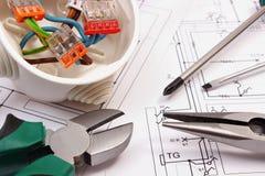 Prac narzędzia i elektryczny pudełko z kablami na budowa rysunku dom Fotografia Stock