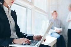 praca biurowa Kobieta z laptopem i drużynowy dyskutuje projekt na tle zdjęcie stock