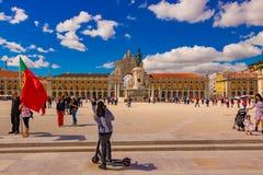 Praca de comercio σε μια όμορφη φωτεινή ημέρα με το σαφή μπλε ουρανό και τα σύννεφα και πολύ τουρίστα που εξερευνούν τον Η ημερομ στοκ εικόνα