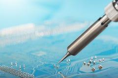 Praca W Toku Lutować elektronicznego obwodu deska z elektronicznymi składnikami lutownicza stacja Inżyniery naprawiają obwód bo zdjęcie royalty free