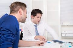 Praca zespołowa: dwa biznesowego mężczyzna siedzi przy biurkiem przy biurem. obraz royalty free