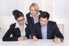 Praca zespołowa między trzy ludźmi biznesu przy biurkiem przy biurem. zdjęcie royalty free
