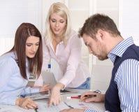 Praca zespołowa przy biurem z trzy młodymi biznesmenami. Fotografia Stock