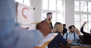 Praca zespołowa przy nowożytnym miejsce pracy konwersatorium, uśmiechnięty w średnim wieku biznesmena trener prowadzi wieloetnicz zdjęcie wideo