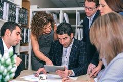 Praca zespołowa przyglądający biznesowy dokument w elektronicznej pastylce zdjęcia royalty free