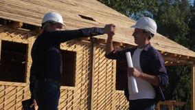 Praca zespo?owa Pojęcie budynek buduje architekta zwolnionego tempa wideo Dwa mężczyzn budowniczego styl życia w hełmach trząść r zdjęcie wideo