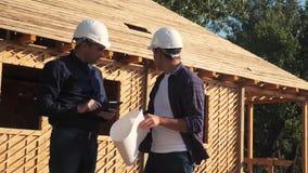 Praca zespo?owa pojęcie budynek buduje architekta zwolnionego tempa wideo dwa mężczyzn budowniczy w hełmach studiuje domowego pla zdjęcie wideo