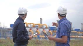 Praca zespo?owa przemysł produkcji stacji benzynowy pojęcie zwolnionego tempa wideo dwa inżyniera w hełma styl życia studiują zbiory