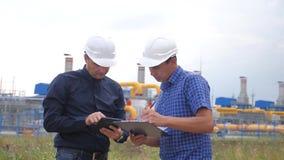 Praca zespo?owa przemysł produkcji stacji benzynowy pojęcie zwolnionego tempa wideo Dwa inżyniera w hełmach studiują pracować z zdjęcie wideo