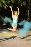 Prachtig donkerbruin model die met het exploderen blauwe Holi springen powd Royalty-vrije Stock Afbeeldingen