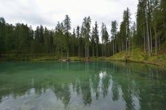 Prachtig smaragdgroen-gekleurd meer met houten brug en cabine dichtbij Cortina D ` Ampezzo stock afbeeldingen