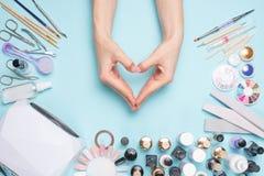 Prachtig verzorgde vingernagels in de vorm van een hart op de Desktop met hulpmiddelen voor manicure Zorg over het noorden stock foto's