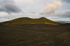 Prachtig vulkanisch landschap op de weg aan Landmannalaugar, IJsland Zwarte vulkanische die as door groene mossen wordt behandeld royalty-vrije stock fotografie