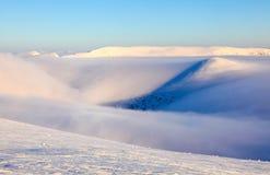 Prachtige de winterzon hoog in de bergen op mooie bossen en gebieden Bergen in mist Ochtendlichten Royalty-vrije Stock Afbeeldingen